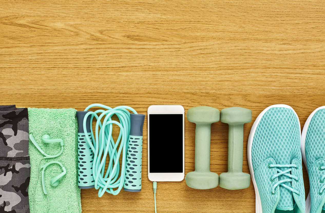 Flat lay of sports equipment with smart phone on wood