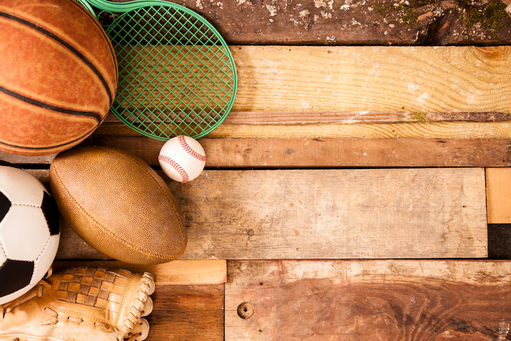 Sports concept. Basketball, tennis racket, baseball, glove, soccer ball, football to left of unique wooden boards background. Selective focus on wooden boards.