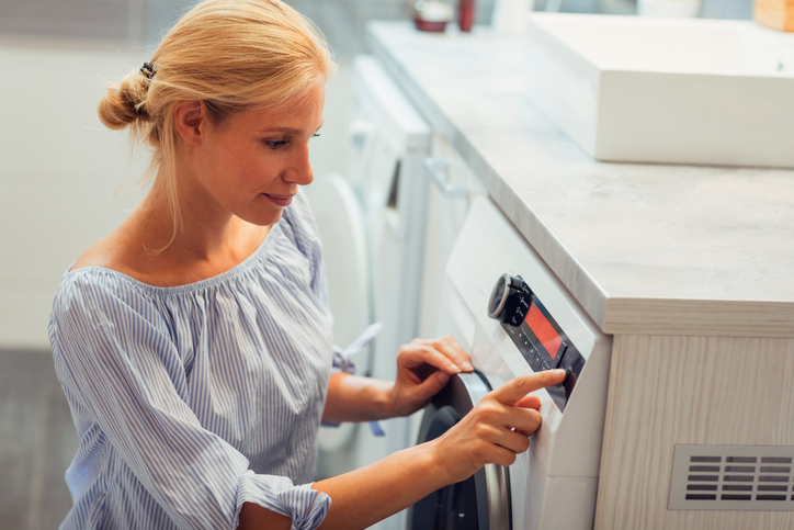 Mid adult woman doing laundry. Turning on or off washing machine.